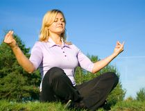 Girl meditation on the meadow stock photography