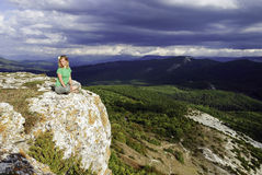 Girl meditation at the mountains. Blue sky Stock Photography