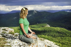 Girl meditation at the mountains. Blue sky Royalty Free Stock Image