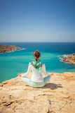 Girl in a meditation pose. At the coast Stock Image