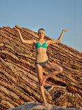 Girl meditation on rock background during sunset. The yoga pose. Fitness and a healthy lifestyle. royalty free stock image