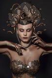 Girl Medusa headdress of gold color on a black background.  royalty free stock images