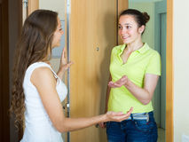 Girl meeting girlfriend at the door. Cheerful young women meeting girlfriend at the door royalty free stock image