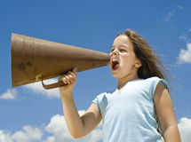 Girl and megaphone. Girl shouting with a megaphone against blue sky Royalty Free Stock Photography