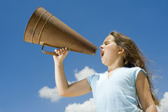 Girl and megaphone. Girl shouting with a megaphone against blue sky Stock Photos