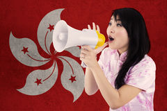Girl with megaphone and flag of Hong Kong Royalty Free Stock Images