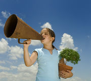 Girl with megaphone and small tree. Young girl holding and small tree and shouting with a megaphone against blue sky Royalty Free Stock Image