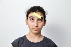 Girl with memo posts on her forehead. Little girl with memo posts on her forehead Royalty Free Stock Image