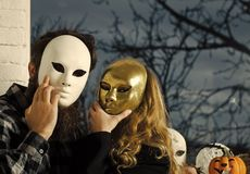 Girl and man hide face with masque Royalty Free Stock Photo