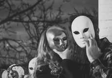 Girl and man hide face with masque Royalty Free Stock Image