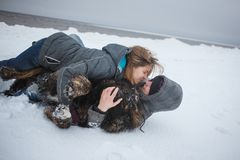 Girl and man kissing and playing with dog in snow, Happy holidays, love moments and rest in nature in winter. Girl and men kissing and playing with dog in snow Royalty Free Stock Photo