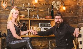 Girl and man on relaxed faces enjoy warm atmosphere. Couple spend romantic evening in gamekeepers house, wooden interior. Girl and men on relaxed faces enjoy stock images