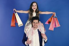 Girl and man with smiling faces hold shopping bags on blue background. Schoolgirl sits on dads shoulders. Shopaholics. Girl and men with smiling faces hold stock photo
