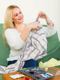 Girl mending linen. Attentive  american girl on couch mending linen and smiling Royalty Free Stock Photography