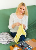 Girl mending linen. Attentive blond girl on couch mending linen and smiling Stock Photography