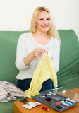 Girl  mending linen. Attentive  longhair girl on couch mending linen and smiling Stock Photos