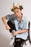 Girl mending sock. S with hair curlers Stock Photo