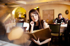 Girl with a menu in a restaurant Royalty Free Stock Photography