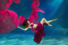 Girl mermaid. Underwater scene. A woman, a fashion model in the. Water in a beautiful dress swims like a fish stock photos