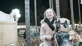 Girl on a merry go round. A beautiful young girl is sitting on a horse on a carrousel stock video footage
