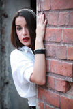 Girl with mesh on head and hand on the brickwall. Senzual style. Fashion shot. Royalty Free Stock Photo
