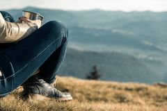 Girl with a metal cup sits on a background of mountains royalty free stock images