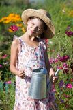 Girl with metal watering can in summer garden Stock Photo