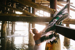 Girl with mexican blanket under pier Royalty Free Stock Image