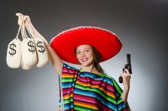 Girl in mexican poncho holding handgun and money Royalty Free Stock Image