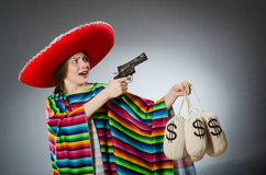 Girl in mexican poncho holding handgun and money Stock Image