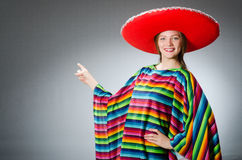 The girl in mexican vivid poncho against gray Royalty Free Stock Photos