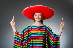 Girl in mexican vivid poncho against gray Royalty Free Stock Photos