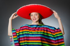 The girl in mexican vivid poncho against gray Stock Photo