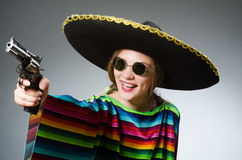 The girl in mexican vivid poncho with handgun Royalty Free Stock Photography