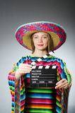The girl in mexican vivid poncho holding clapboard Stock Photos