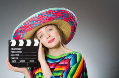 The girl in mexican vivid poncho holding clapboard Royalty Free Stock Photo