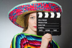 The girl in mexican vivid poncho holding clapboard Royalty Free Stock Images