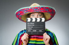 The girl in mexican vivid poncho holding clapboard Royalty Free Stock Photography