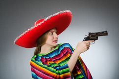 The girl in mexican vivid poncho holding handgun Royalty Free Stock Images