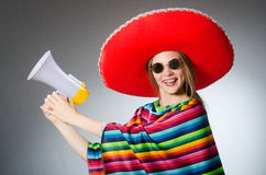 Girl in mexican vivid poncho holding loudspeaker Stock Photos