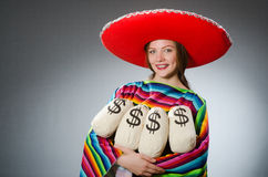 Girl in mexican vivid poncho holding money bags Stock Image
