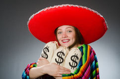 Girl in mexican vivid poncho holding money bags Royalty Free Stock Images