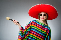 Girl in mexican vivid poncho with maracas against Stock Images