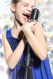 Girl with microphone. The girl in a blue dress singing karaoke Royalty Free Stock Photos