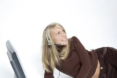 Girl / microphone headset. Girl lying down on her side next to a flat-screen monitor has on a microphone headset Royalty Free Stock Images