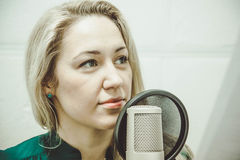 The girl at the microphone in the Studio Royalty Free Stock Photography