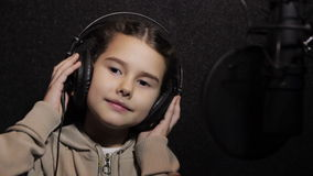 Girl with a microphone. Stylish young girl singing with a microphone in music studio stock video