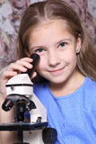 Girl with microscope Royalty Free Stock Photography