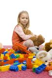 Girl in the middle of toy-mess Royalty Free Stock Photos