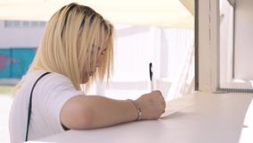 Girl in midst of beach season, signs questionnaire. CU, 4k, Portrait: Young beautiful girl in the summer, in the midst of a beach season, signs a questionnaire stock footage
